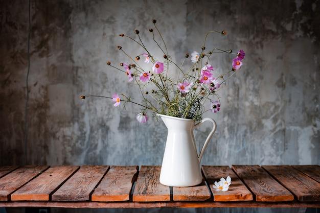 Красивые букеты полевых цветов на деревянном столе на холодной бетонной стене.