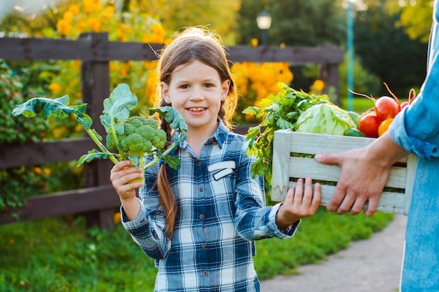 Маленькая девочка детей держа маму корзину свежих органических овощей с домашним садом.