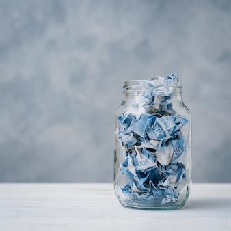 Российский рубль мятые бумажные деньги лежат в стеклянной банке