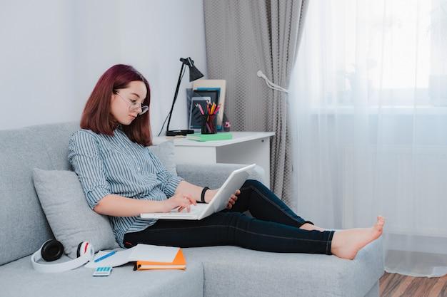 Студент софы живущей комнаты пола молодого девочка-подростка лежа изучая домашнюю работу при ее компьтер-книжка делая домашнюю работу.