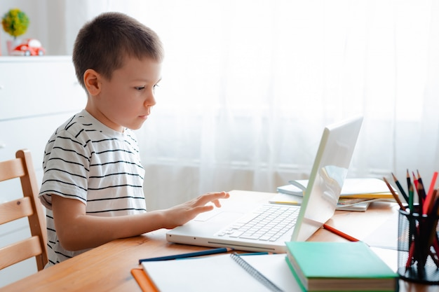 Дистанционное обучение онлайн-образование. школьник учится на дому и делает домашнее задание. домашнее дистанционное обучение