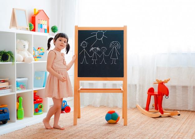 子供部屋に女の子が黒板を持って立ち、チョークで家族を描いています。