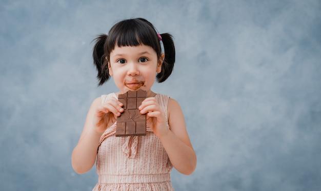 小さな女の赤ちゃんはチョコレートを食べ、彼女の指をなめる