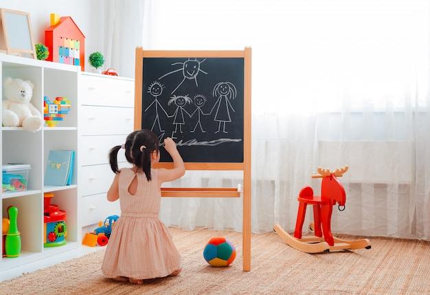 女の子は黒板で子供部屋に立って、チョークで家族を描きます。