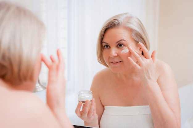 彼女の顔にクリームを適用する年配の女性