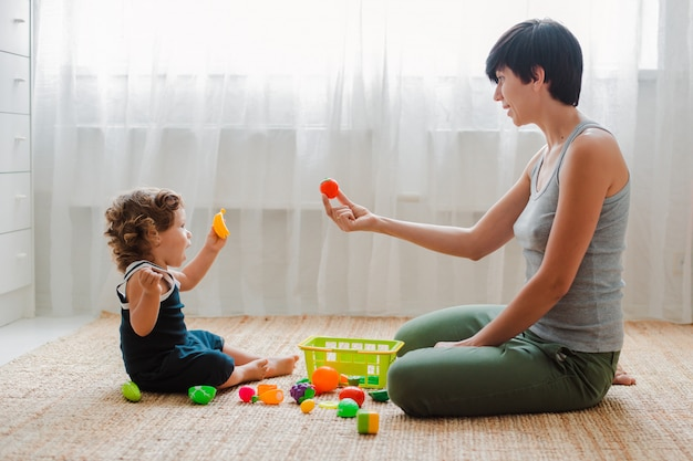 母と子が床で遊んで