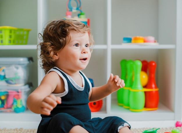 Малыш играет на полу комнаты с развивающими пластиковыми игрушками.