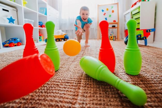子供男の子は家のボウリング場にボールを投げ、ボウリングのピンを壊します