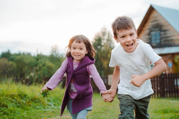兄と妹は村の家で手で走っています。私の祖母と一緒に村での休暇。