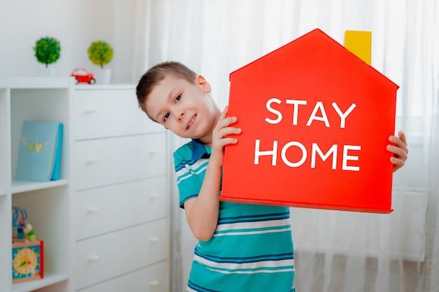 メモの言葉で家の赤いモデルを保持している子供男の子手