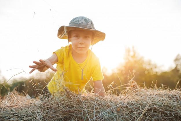 Маленький мальчик сидит на высоте большого стога сена в деревне. ребенок фермер.