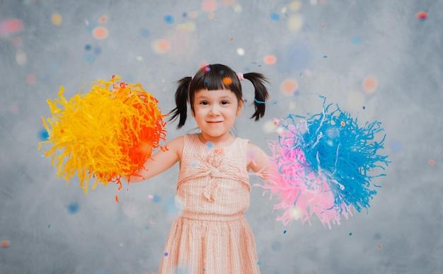Маленькая девочка весело подбрасывает разноцветную мишуру и конфетти на серый