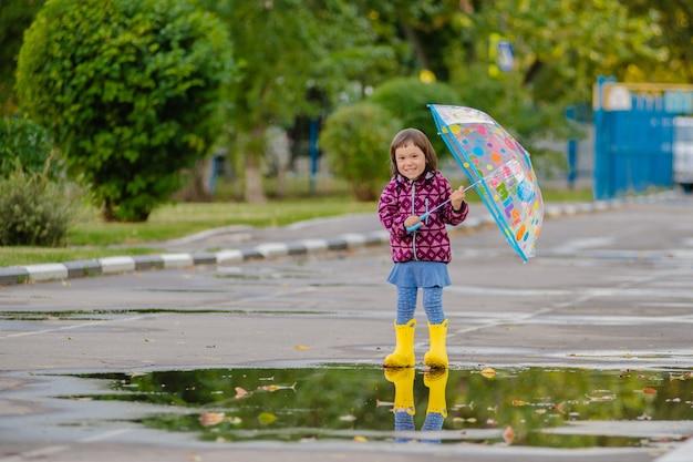 色とりどりの傘がゴム長靴で水たまりをジャンプして笑って幸せな面白い子