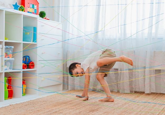 男の子の兄弟、フレンドチャイルドはロープの網、屋内でゲームの障害物クエストを登ります。