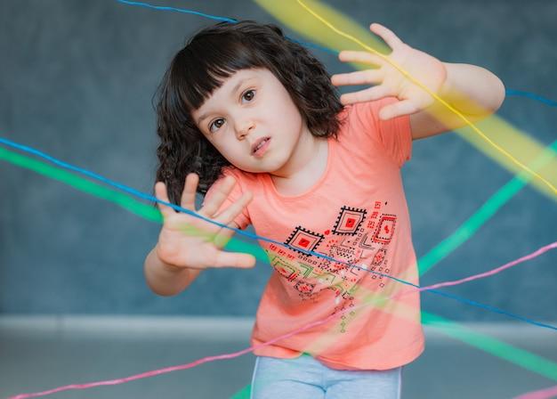 小さな女の子の子供が屋内でロープウェブゲームの障害物クエストを登っていきます。