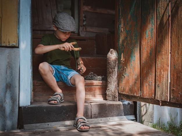 帽子をかぶった少年はパチンコで狙いを定め、狙いを定めます。休暇中に村で子供として遊んでください。