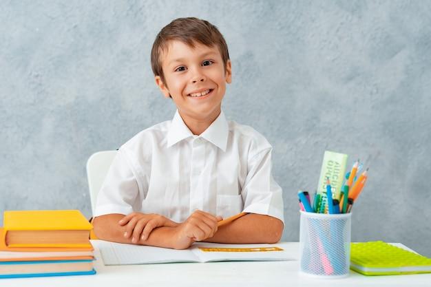 学校に戻る。幸せな笑顔の学生が机に描画します。
