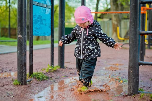 Ребенок проходит через лужи