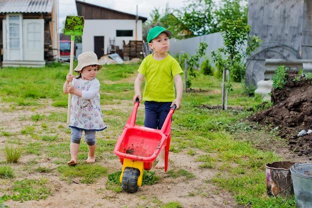 子供たちは庭でシャベルと手押し車を使って仕事をしています