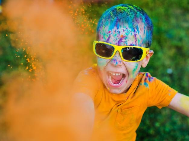 Ребенок в очках бросает краски холи