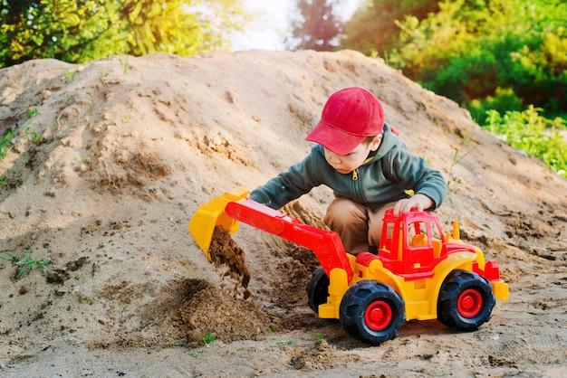 Ребенок играет в песке экскаватор