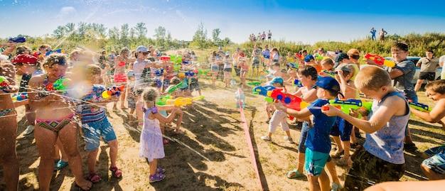 美しい晴れた日に水の大砲と屋外で遊ぶ子供たち