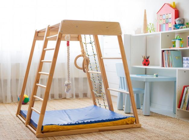 Детская комната с деревянным спортивным комплексом с лестницей, кольцами и веревкой.
