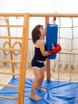 Маленький ребенок занимается боксом на деревянном домашнем спортивном комплексе.
