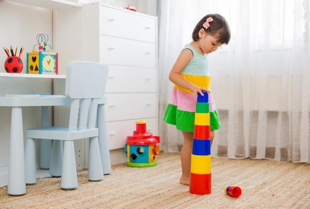 Счастливые дети дошкольного возраста играют с красочными пластиковых игрушек блоков.