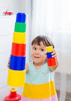 就学前の幸せな子供たちはカラフルなプラスチック製のおもちゃのブロックで遊ぶ。