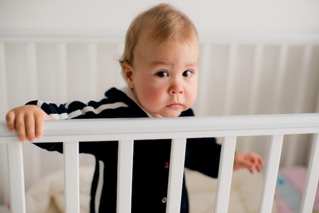 ベビーベッドに立っている悲しい子供
