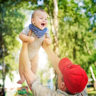 父の楽しい幸せな息子が投げます。晴れです