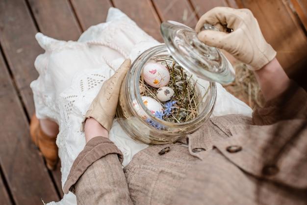 Декоративные пасхальные яйца в стеклянной банке крупным планом на коленях и в руках девушки в винтажной одежде.