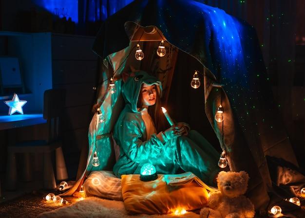 Девочка-подросток в виде аниме сидит в игровой палатке дома. декорации с фантастическим освещением гирлянды