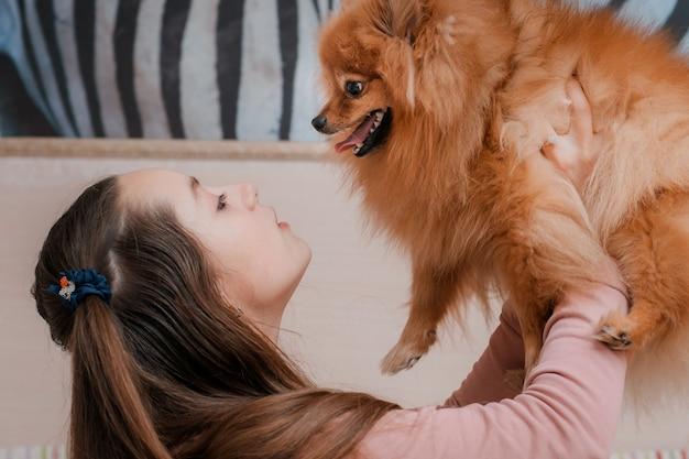 Девочка-подросток с собакой породы шпиц радуется с домашним животным на полу.