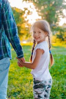 公園で彼女の父の手を握って小さな女の子子供娘