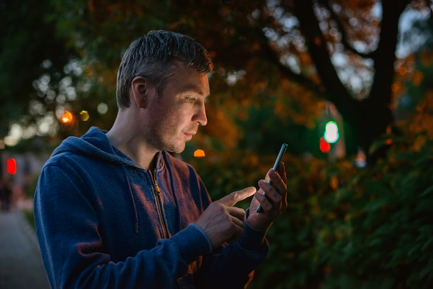 流行に敏感な人が街で夜に携帯電話で話しています。