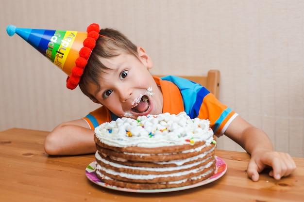 子供の男の子が彼の誕生日ケーキを食べています。