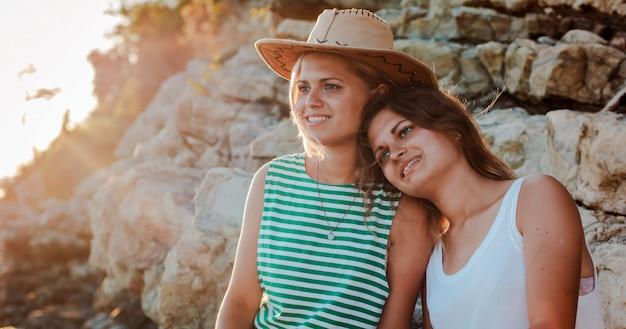 海の海岸の岩の上の流行に敏感な帽子の若い陽気な女性。