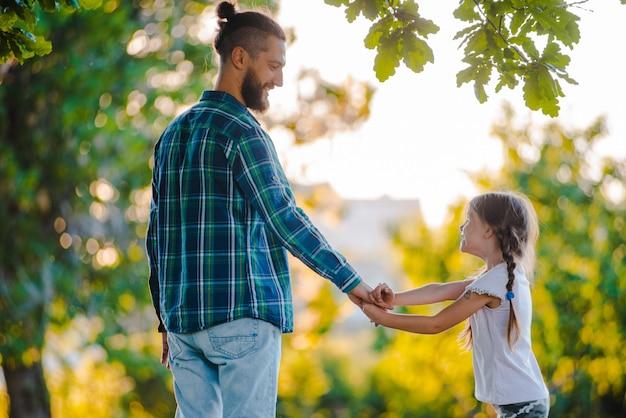 少女の子供の娘が彼女の父の手を握って、夕暮れ時の自然の。