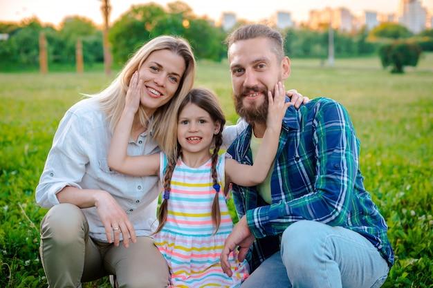 緑の自然の中で外で一緒に時間を過ごす幸せな若い家族。