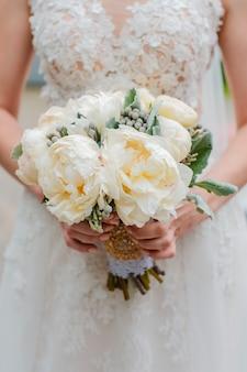 新婚カップル。結婚式の日。手に花嫁の花束、新郎の抱擁。