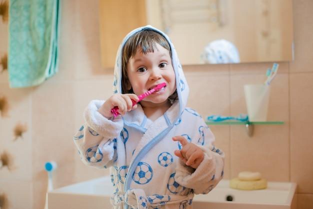小さな女の子の子供が浴室で歯を磨きます。口腔衛生。