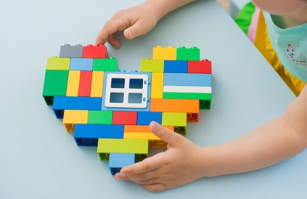 子供の手の中にある明るいハート型のビルディングブロック。教育玩具