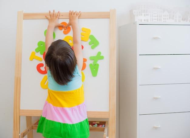 アルファベットの文字を勉強している幼児の女の子。