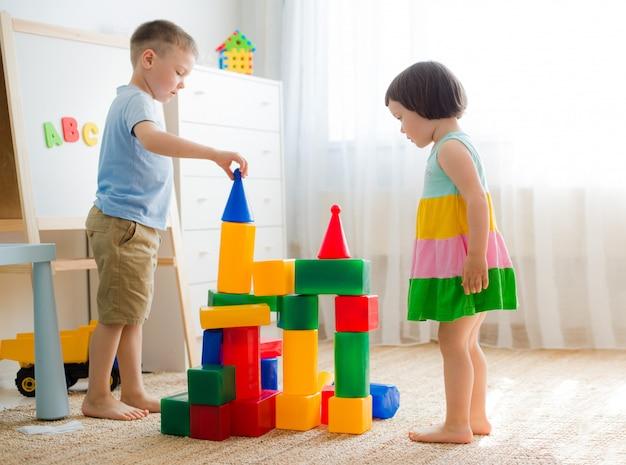 Счастливые дети дошкольного возраста играют с игрушечными блоками.