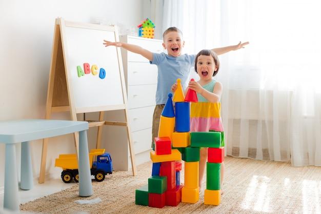 幸せな就学前の子供たちはおもちゃのブロックで遊ぶ。