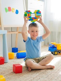 床に座っている子供が遊んでいます。明るいビルディングブロックは、子供たちの心の手を形作ります。