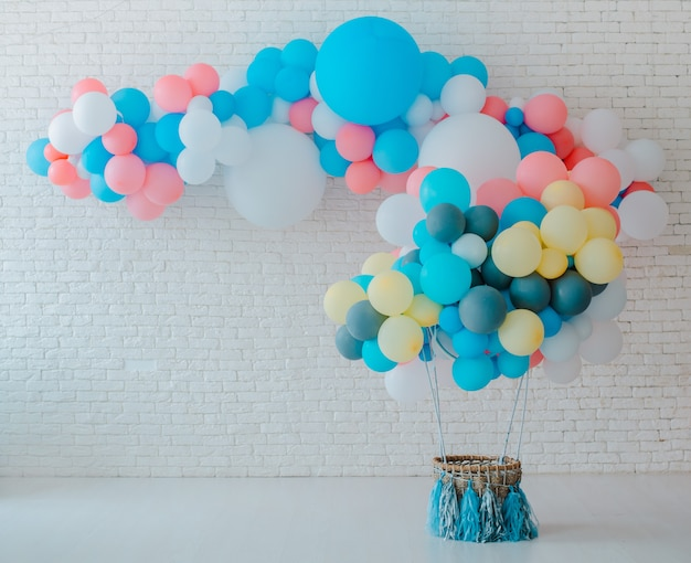 Воздушные шары и мороженое корзину на праздничный белый кирпич с большой пряничный человечек.