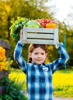 新鮮な有機野菜の箱を保持している少女